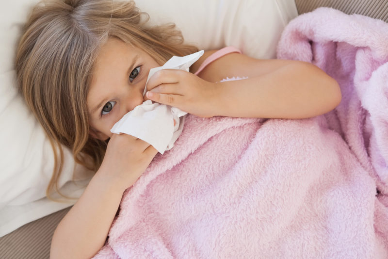 Sick little girl with tissue in her hand