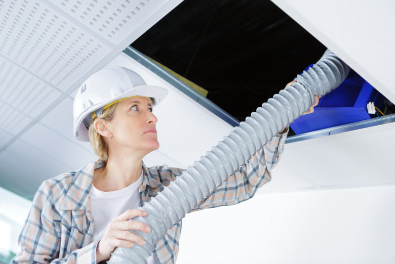 female doing maintenance on air conditioning system