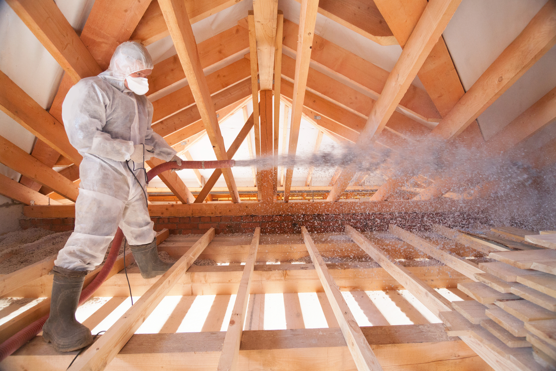 A man spraying insulation in an attic.