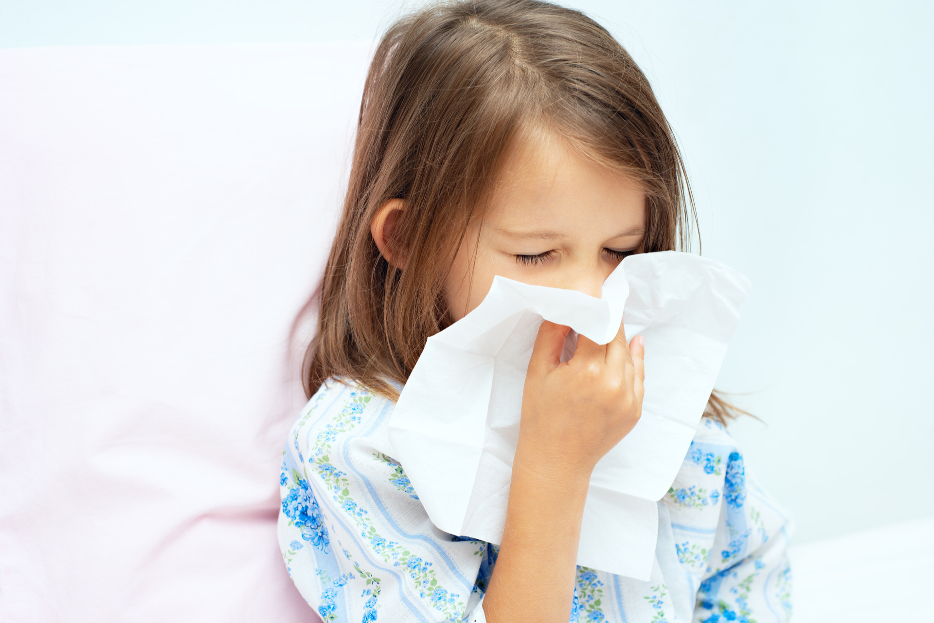 A girl with an allergy sneezes.